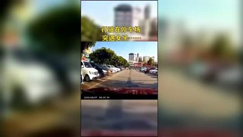 视频车行驶在停车场,突遇女子骑车穿行