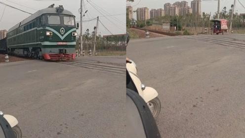 火车即将到来,男子不顾危险,驾驶三轮车淡定通过匝道