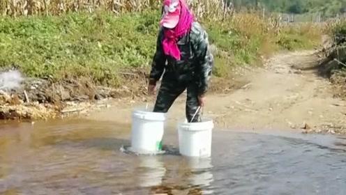 真是佩服大姐的智慧,没有雨鞋也能安全过河,全靠两个大桶来凑?