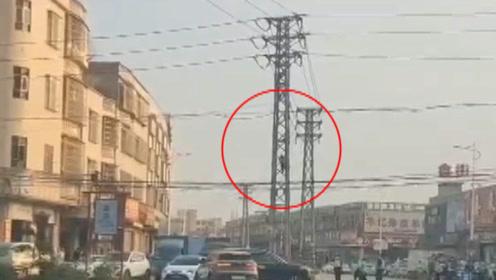 为躲避交警查处,男子竟弃车直接爬上高压塔,路人看得目瞪口呆
