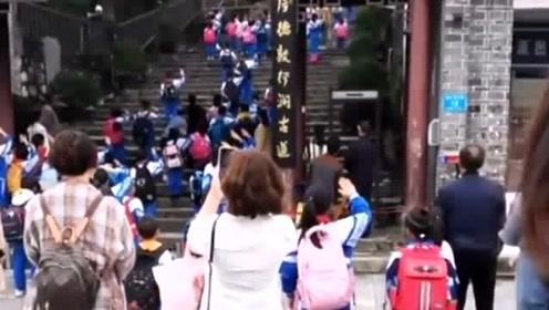 学校里传出了国歌声,小学生纷纷停下脚步举手