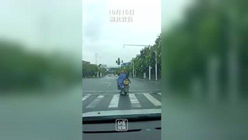 揪心!小女孩跌落电动车家长浑然不觉,后车司机狂按喇叭一路护送