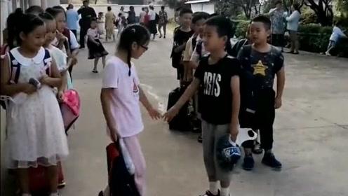 开学了,男同学拉女同学的手进入教室