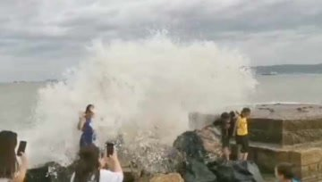 """台风""""白鹿""""来袭,海边掀巨浪,游客仍在看海"""