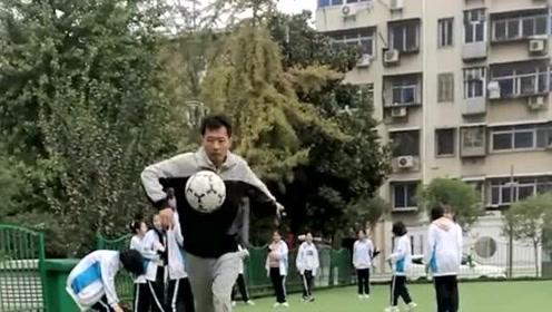 体育老师展示颠球技巧,不愧是专业的,这么高还能接住再次踢起来!