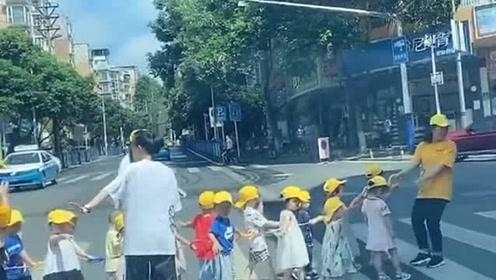 祖国的花朵过马路,小朋友手牵手跟在老师后面