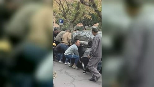 轿车轮胎压着脚啦!23名路人火速抬车救小男孩