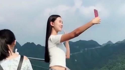 美女在玻璃桥上自拍,手机被旁边的游客撞掉了